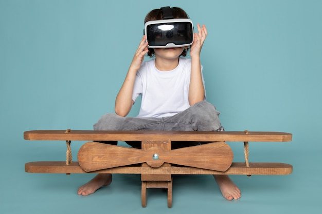 Front view child boy playing vr goggles in white t-shirt and grey jeans on blue