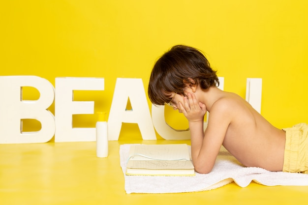 Front view child boy sitting on the white towel along with word beach on the yellow desk