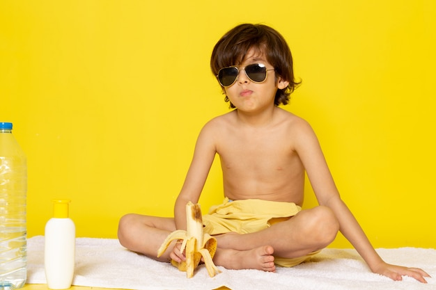 Front view child boy in sunglasses on the yellow desk