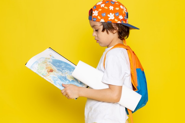 Front view child boy in white t-shirt and baseball cap holding map on yellow