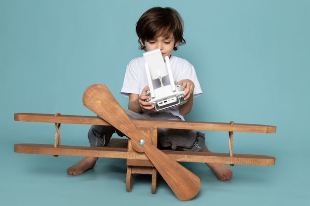 Front view child boy in white t-shirt holding remote controller on blue