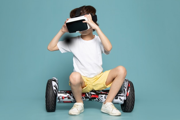 A front view child boy in white t-shirt playing vr on segway on the blue space