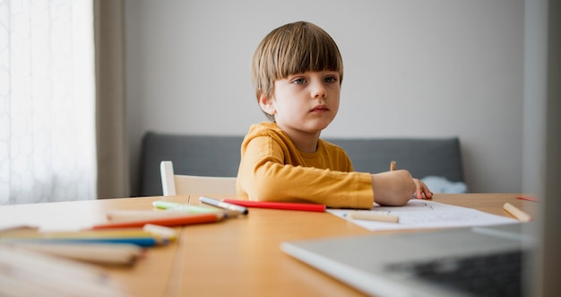 Front view of child at desk drawing