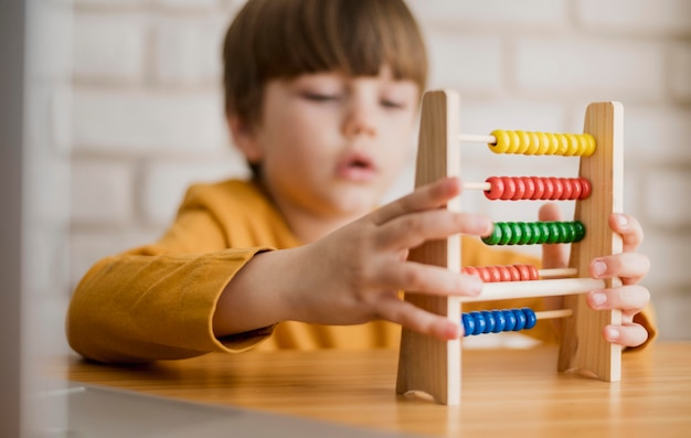 Front view of child at desk using abacus