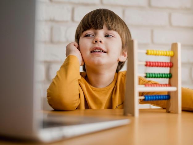 Front view of child at desk with laptop and abacus