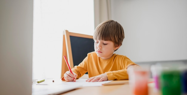 Front view of child drawing at desk