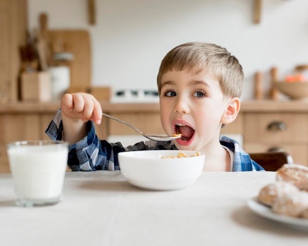 Front view child eating cereals with milk