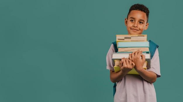 Вид спереди ребенка, держащего стопку книг с копией пространства