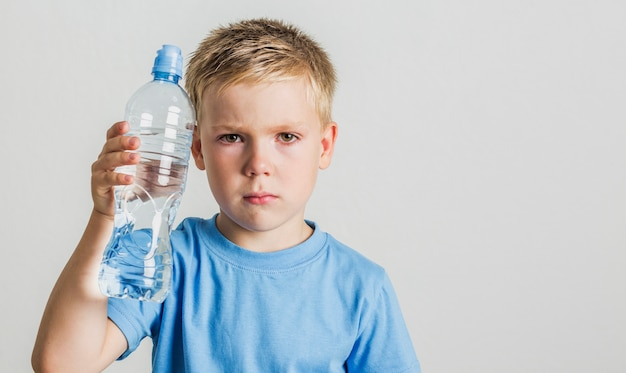 Front view child holding a water bottle