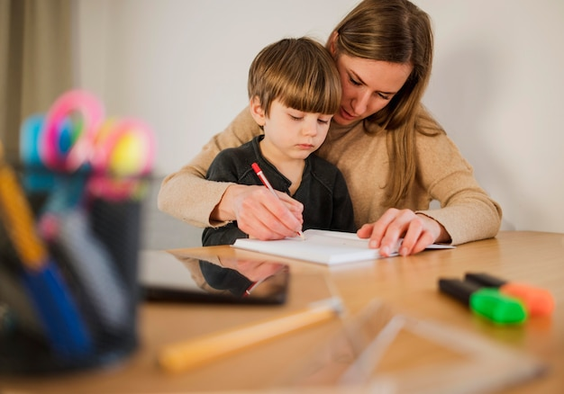 Front view of child at home with female tutor