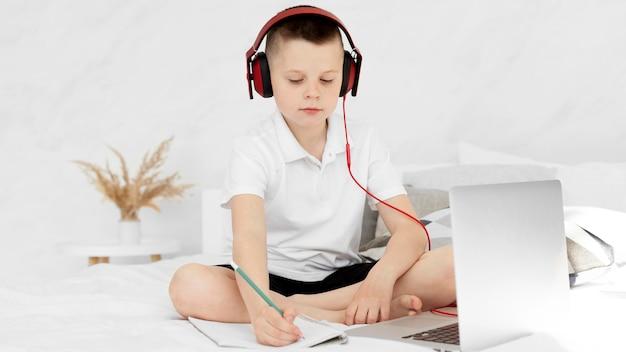 正面の子供がオンラインで学習し、ヘッドフォンを使用