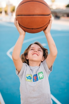 Front view of child playing basketball