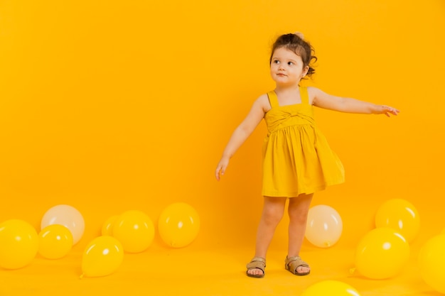 Front view of child posing with balloons and copy space