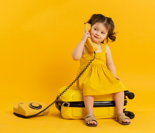 Front view of child posing with telephone and luggage