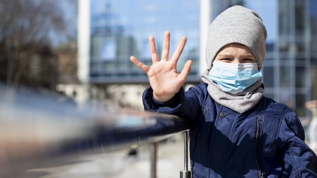 Vista frontale del bambino che mostra la mano mentre indossa la maschera medica fuori