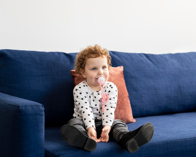 Front view of child sitting on the sofa