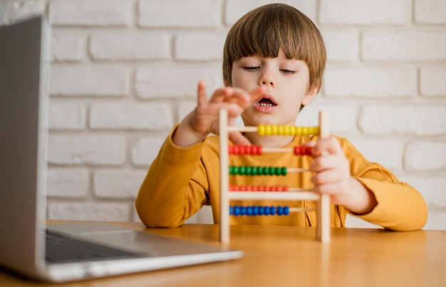 Front view of child using abacus with laptop