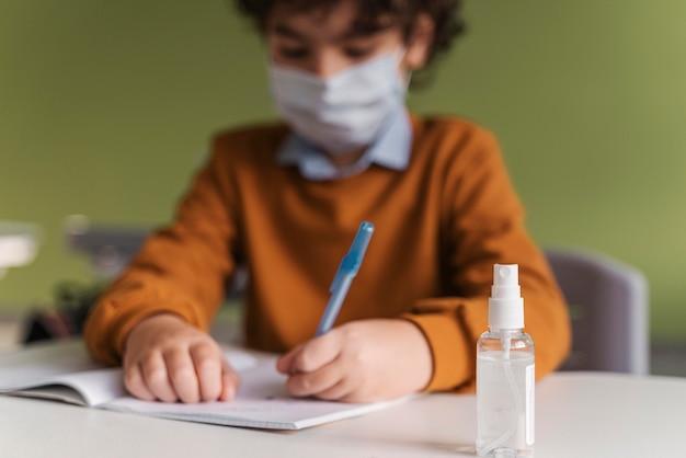 Vista frontale del bambino con mascherina medica in classe con bottiglia di disinfettante per le mani sulla scrivania