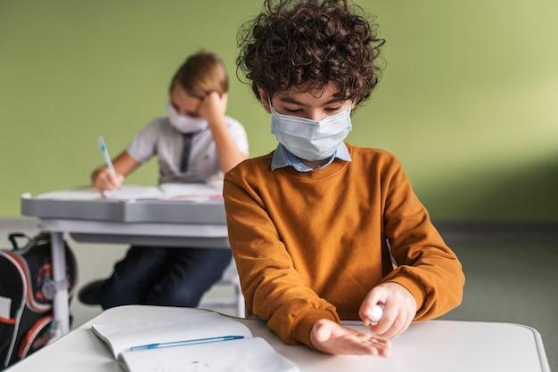 Vista frontale del bambino con mascherina medica che disinfetta le mani in classe