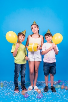Front view of children holding balloons and gift standing on blue background