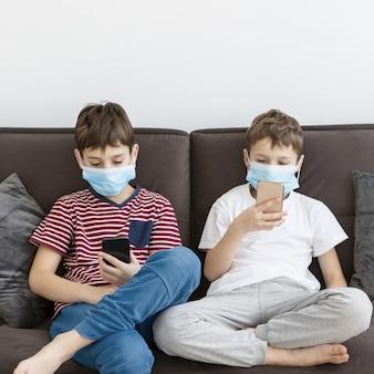 Vista frontale dei bambini a casa indossando maschere mediche e giocando su smartphone