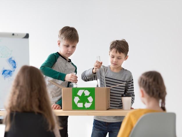 正面図の子供たちがリサイクル方法を学ぶ
