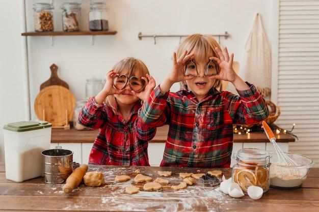 家で一緒にクッキーを作る正面図の子供たち