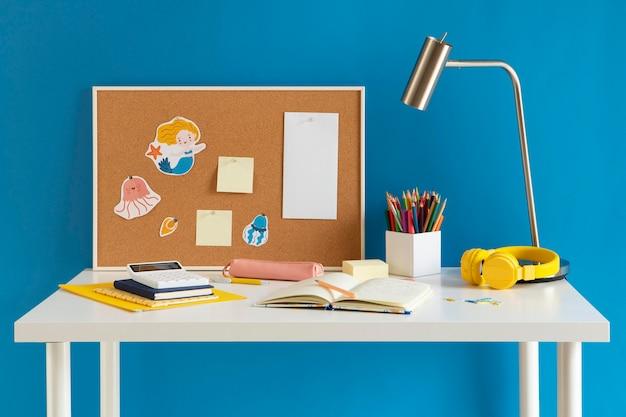 Vista frontale della scrivania per bambini con lampada e taccuino