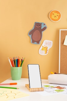 Front view of children's desk with smartphone and pencils
