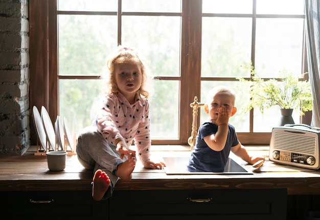 Front view children sitting on countertop
