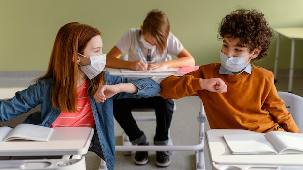 Front view of children with medical masks doing the elbow salute in class