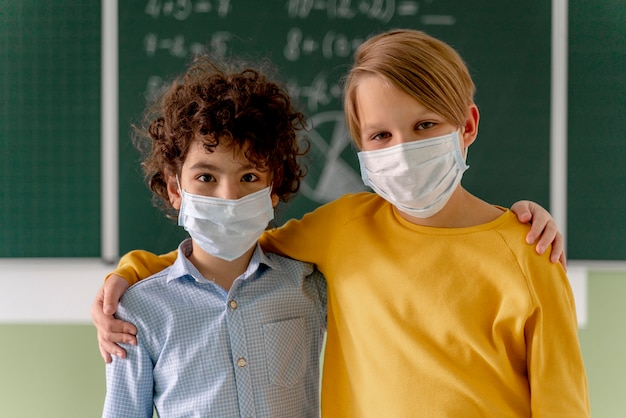 Front view of children with medical masks posing in classroom in front of blackboard