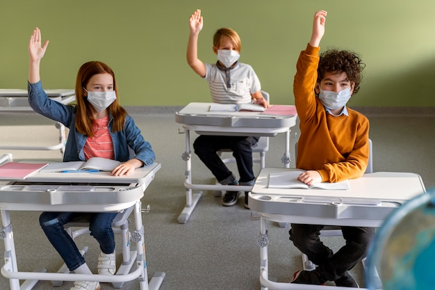 Front view of children with medical masks in school raising their hands