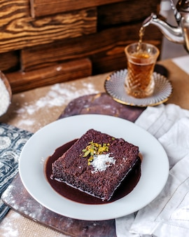 Front view choco cake tasty inside white plate along with hot tea on the brown surface