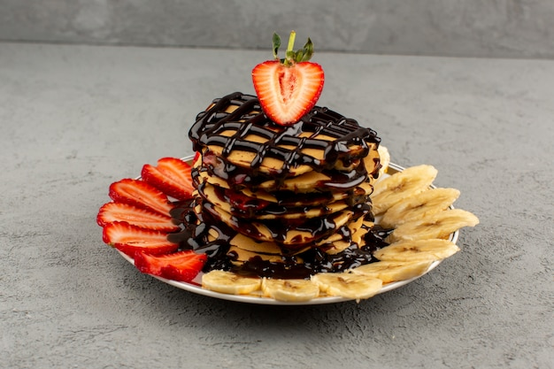 Front view choco pancakes with red sliced strawberries and bananas inside plate on the grey floor
