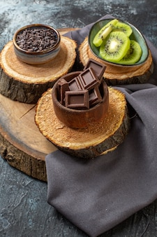 濃い灰色の表面にスライスされたキウイと正面図のチョコレートバー