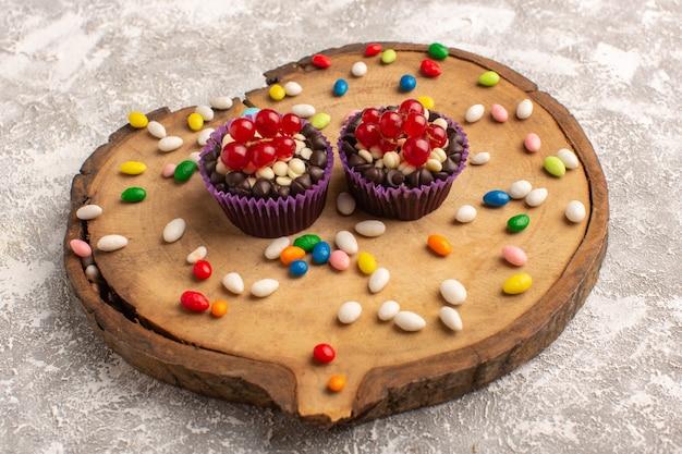 Vista frontale dei brownies al cioccolato con caramelle sul bordo di legno