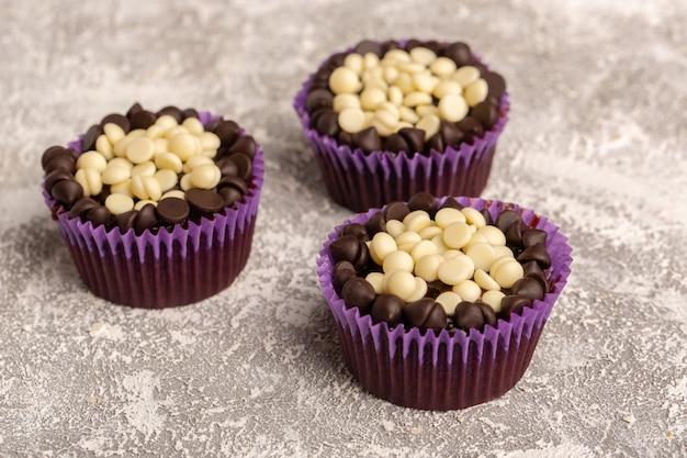 Vista frontale di brownies al cioccolato con scaglie di cioccolato bianco e fondente sulla superficie luminosa