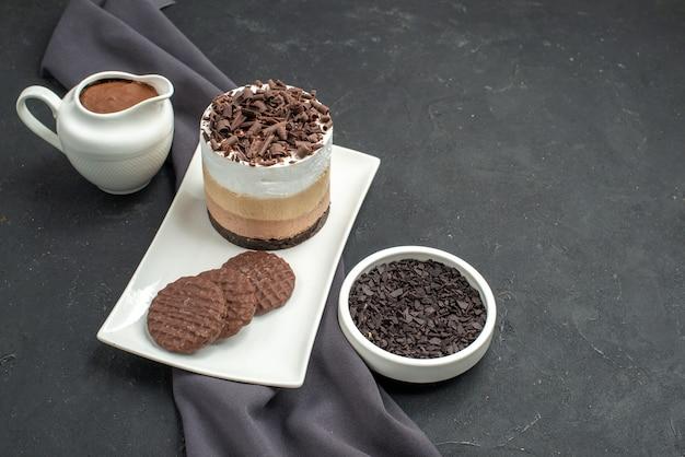 Vista frontale torta al cioccolato e biscotti su ciotole di piatto rettangolare bianco con scialle viola al cioccolato su sfondo scuro isolato spazio libero