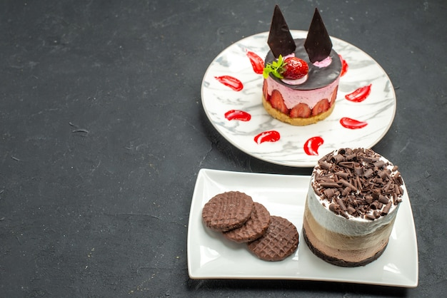 Front view chocolate cake and biscuits on white rectangular plate and cheesecake on white oval plate on dark