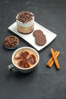 Front view chocolate cake and biscuits on white rectangular plate cup of coffee cinnamon sticks bowl