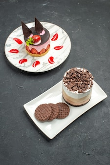 Front view chocolate cake and biscuits on white rectangular plate and strawberry cheesecake on white oval plate