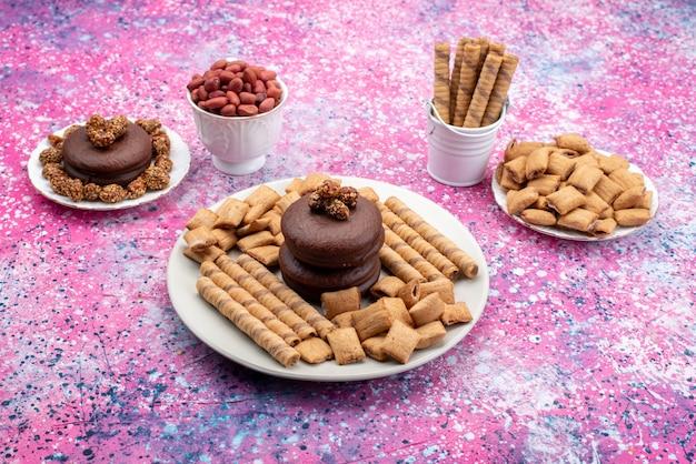Vista frontale della torta al cioccolato con biscotti e patatine sulla superficie colorata