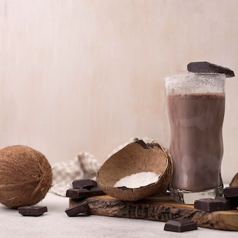 Front view of chocolate and coconut milkshake glass with copy space