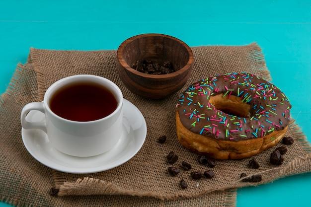 Vista frontale della ciambella al cioccolato con una tazza di tè e cioccolatini su un tovagliolo beige