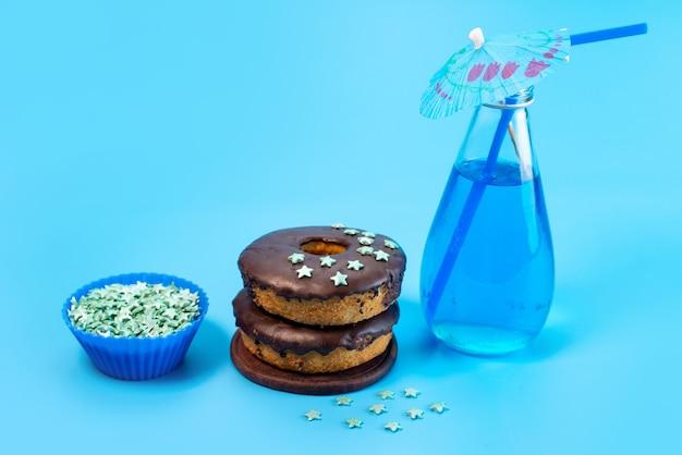 Una vista frontale ciambelle al cioccolato con blu, bevanda sul blu, colore biscotto torta di zucchero