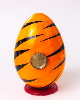 Вид спереди шоколадное яйцо оранжевое с черным цветом с золотой печатью на красной подставке