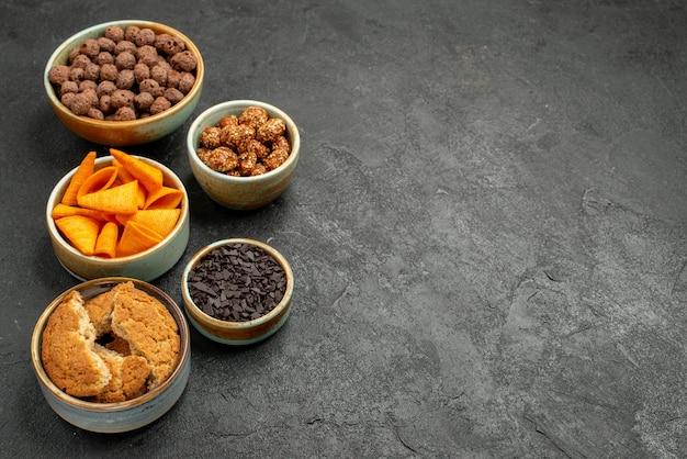 ダークグレーの背景色のスナックナッツにチップスが付いた正面図のチョコレートフレーク