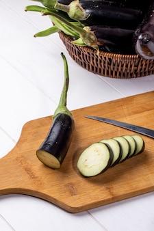バスケットに新鮮なナスをナイフでボード上の刻んだナスの正面図 無料写真