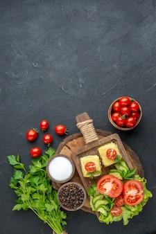 Vista frontale del formaggio di verdure fresche tritate sul tagliere e del fascio di spezie verdi sulla superficie nera